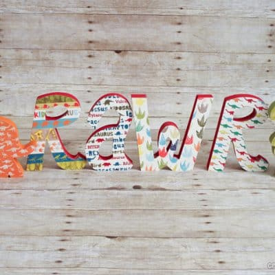 Mod Podge Wooden Dinosaur Letters via createcraftlove.com #modpodge #woodenletters #artsychaos #dinosaurs