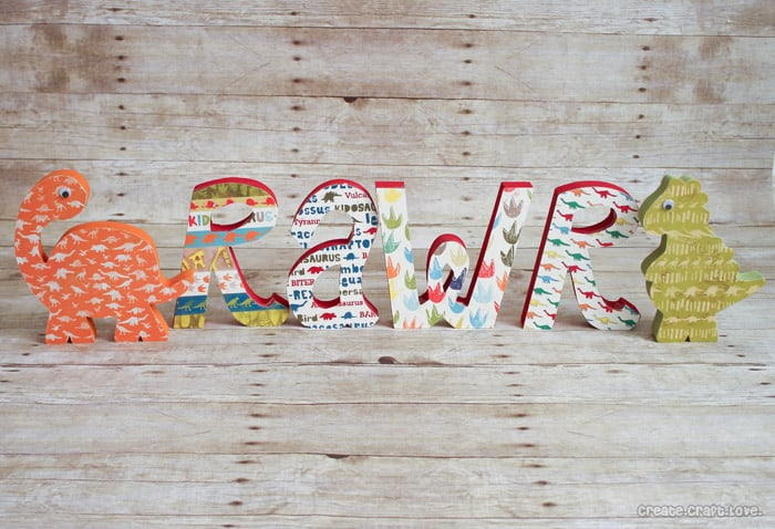 Mod Podge Wooden Dinosaur Letters via createcraftlove.com #modpodge #woodenletters #artsychaos #dinosaurs