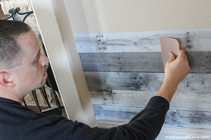 Adhere the wallpaper to the wall to create this wood pallet wall!