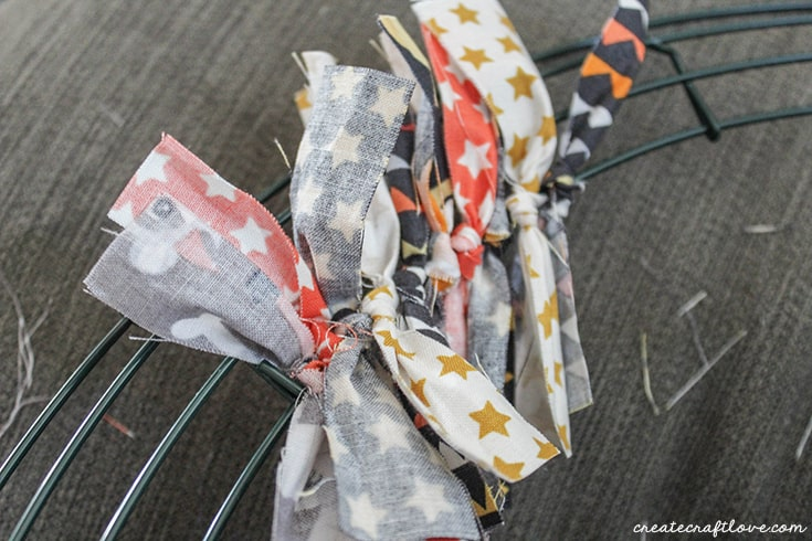 Begin tying your fabric strips for create your Halloween Rag Wreath!