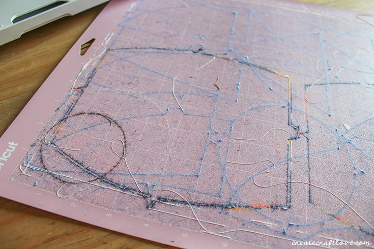Pink fabric mat cuts perfectly despite leftover threads!
