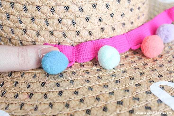 hot glue pom poms to diy beach hat
