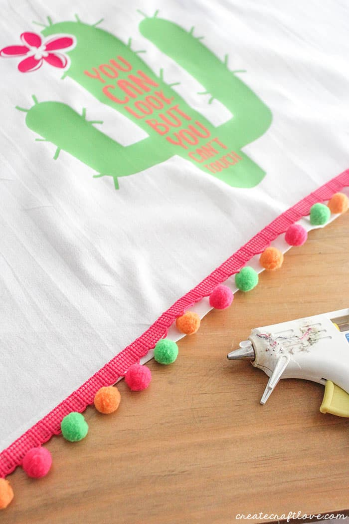 Apply the po pom trim to the bottom of your No Sew Summer Towel!