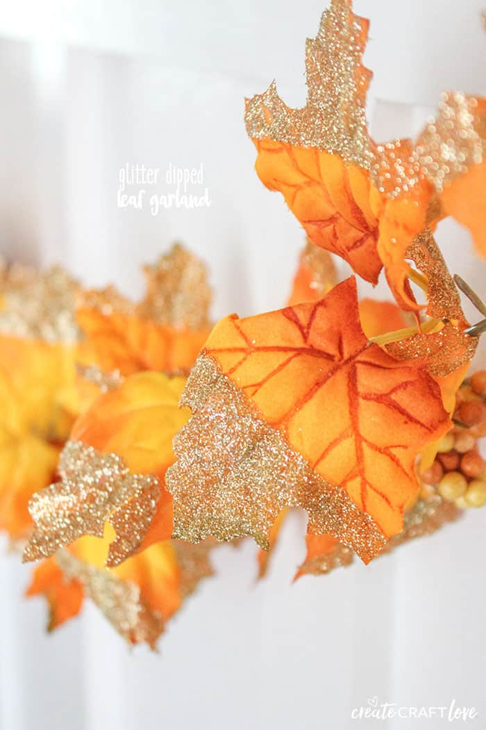 Create this stunning Glitter Dipped Leaf Garland by adding some sparkle to some dollar store garland!