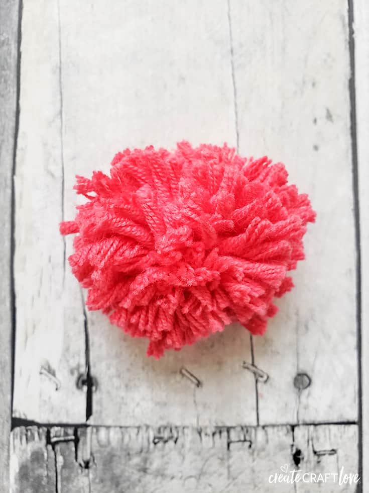 completed pom for body of flamingo pom pom garland